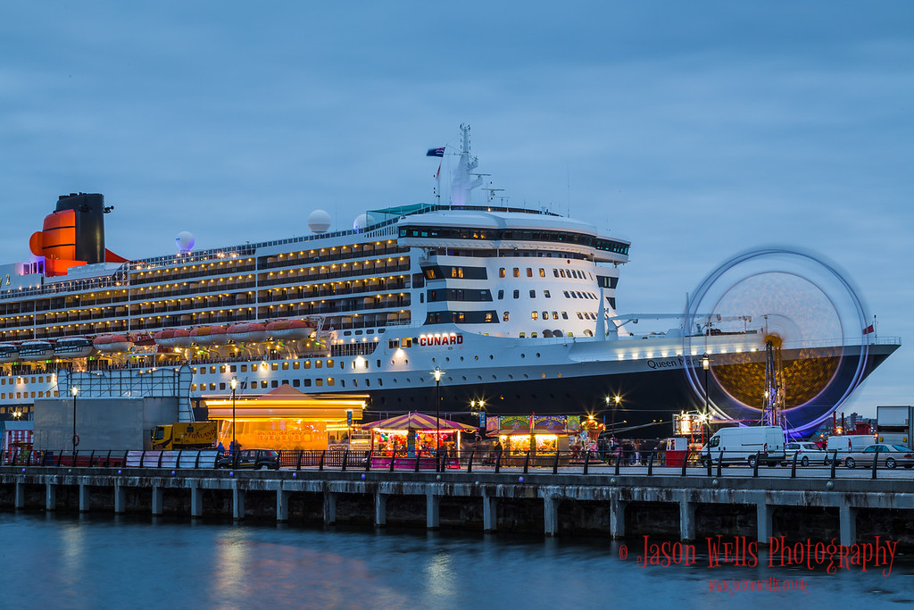 Fairground rides in front of the Queen Mary Two.