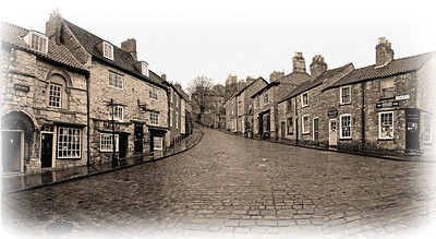 12.04.12 - Back in Time  This is a 3-shot panorama of the familiar view looking up Steep Hill in Lincoln, and I have processed it to be my entry for the current Dgrin Challenge, Photography 100 Years Ago. As well as the monochrome conversion I've added a sepia filter, a pale vignette and noise to give a slightly distressed antique feel. This view itself is slightly too wide for a single shot without a fish eye lens, and also has considerable vertical elevation looking up the hill, hence having to merge three portrait orientation images.  Regarding the thumbs downer that afflicts us from time to time, I have started another discussion thread on Dgrin in a attempt to tackle the issue once and for all. It is clear from the initial response of Smug that most people suffer in silence, but if we want to stop it we need to contact Smug with specific details. Andy, one of Smug's top guys, has offered to deal with this personally. So if this is an issue for you please contact him privately, or join in the Dgrin thread. I'm at pains to point out that this is about serious abuse, not just petty thumbing down or negative comments. The thread is here; http://www.dgrin.com/showthread.php?t=218716
