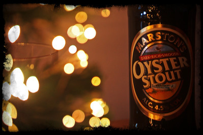 """23.12.10 - Black Gold  Tis the season to be merry, or so the song goes, and this is my poison of choice for Christmas Day. I've had this idea for the current Dgrin challenge """"silver or gold"""", and I thought I'd give it a quick try out this evening when I realised that I'd not taken a Daily yet. I'd like to get the bottle a lot sharper, but a softer focus seems to work with the blurred tree lights and general warm glow of the lighting. The only light was a small scented candle in the glass behind the tree, hence the long exposure. The camera was balanced on a cushion on my knee, I think the tripod might have to come out of the cupboard to get it tack sharp :)"""