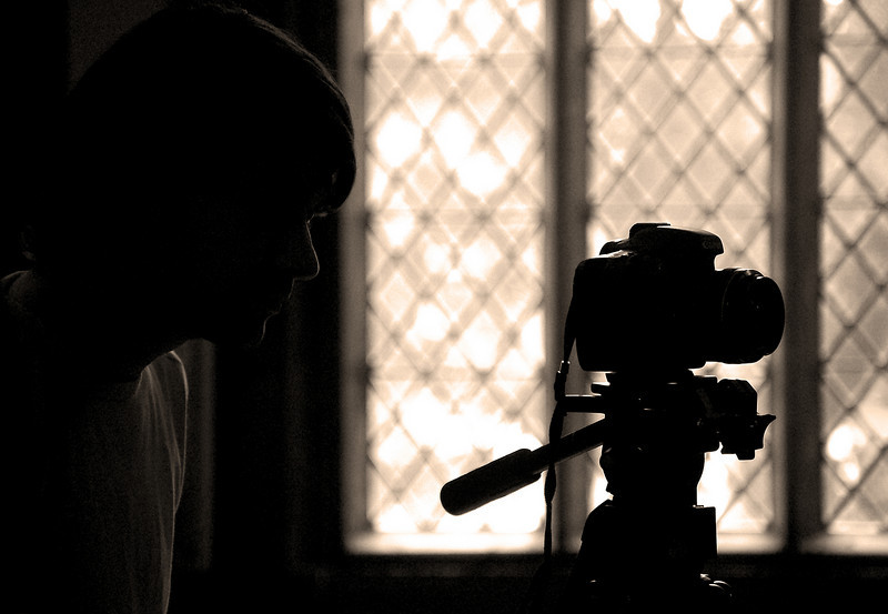 """18.08.10 - Window on the Past<br /> <br /> Today was our last day of shooting in Gainsborough Old Hall. The project that started back in May will soon be completed, just editing and the soundtrack to finish off. This is a shot of Director Nick Loven and his trusty Canon 7D silhouetted against one of the beautiful windows at the Old Hall. The Pilgrim Fathers were sheltered from persecution here. Henry VIII stayed here with his young wife Catherine Howard, and John Wesley preached here. It is a remarkable place. <br /> <br /> Today was extra special for me because my twins were able to come along with me and dress up in period costume. Amy even had a small cameo scene. Huge thanks to Nick and Pauline for making that possible, it is a day they'll never forget.<br /> <br /> My gallery of """"action and behind the scenes"""" shots is here;     <a href=""""http://www.lightanddreamsphotography.com/History/OLD-HALL-TIME-TRAVELLER/12281778_QMhQD#876060804_okncZ"""">http://www.lightanddreamsphotography.com/History/OLD-HALL-TIME-TRAVELLER/12281778_QMhQD#876060804_okncZ</a><br /> <br /> I'll let you know when the film is released."""