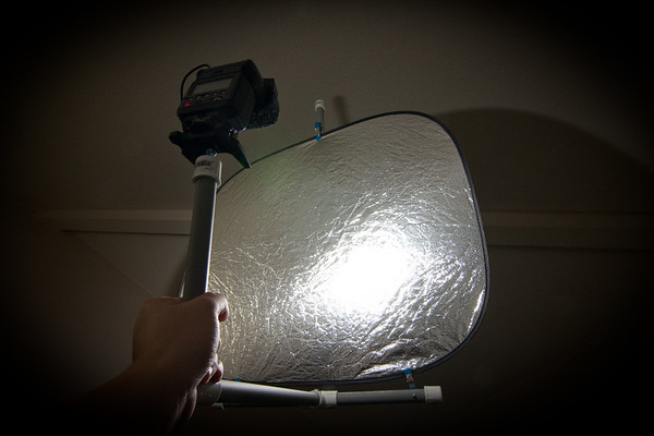 Here's my contraption in all it's PVC glory.  Basically, it's a flash reflector made from a car's sunshade ($3) and about $7 of PVC pipe and fittings from Home Depot.  A little heavier than the California Sunbounce that inspired it, but a whole lot lighter on the wallet.