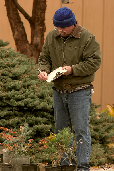 Oct 22nd<br /> <br /> This is just about Don's favorite person. David is a long time propagator of unusual and dwarf conifers, all around great guy as well. He always has new, or potentially new, unnamed conifers that won't be in circulation for years if ever.<br /> <br /> So on one of the nastiest days of the year Don decides he needs a conifer fix and off we go. That little pile of stuff David is standing over is Don's haul for the day, a light one I might add:-) I also had to get a couple goodies, so in that mess is a Ginkgo called Munchkin, only gets about 2' tall and a J Maple not often found in cultivation.  Just to give you and idea Don can spend darn near what a  chunk of good Canon glass costs and fit it all in the Jeep w/o even putting the back seats down:-)