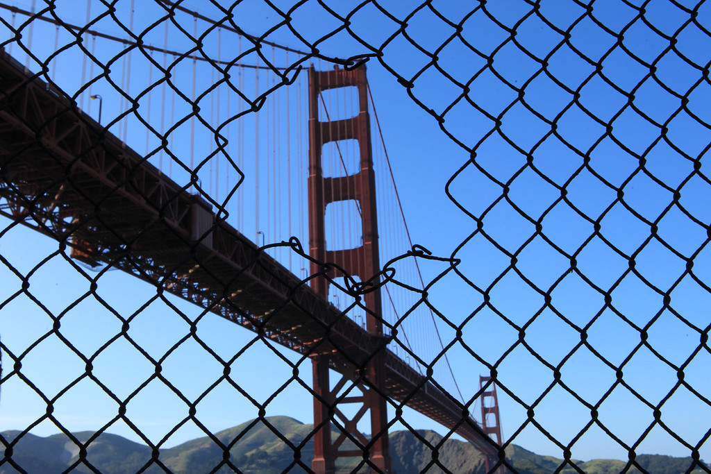One need not generally climb through a hole in the fence to get to the Golden Gate Bridge. There are easier access points. Still so, I like the way the hole created a ready frame for this artistic/engineering masterpiece.