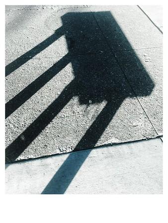 Bench shadow on sidewalk