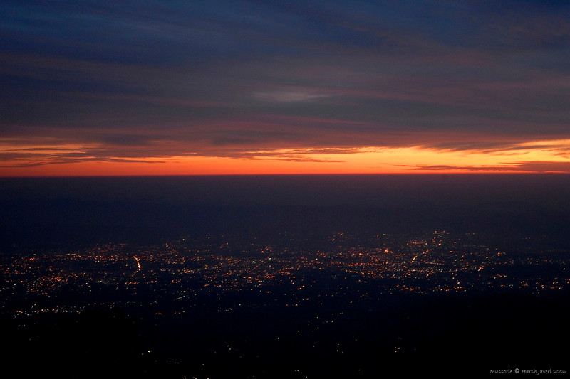 """Sunset over Dehradun from Mussorie bazar<br /> 18 June 2010<br /> <br /> [Not to be confused with the U.S. state Missouri!] Mussoorie is a city about 34 km from Dehradun in the Indian state of Uttarakhand. This hill station, situated in the foothills of the Himalaya ranges, is also known as the Queen of the Hills.  Being at an average altitude of 2,000 metres (6,600 ft), Mussoorie, with its green hills and varied flora and fauna, is a fascinating hill resort. <br /> <br /> <a href=""""http://en.wikipedia.org/wiki/Mussoorie"""">http://en.wikipedia.org/wiki/Mussoorie</a>"""