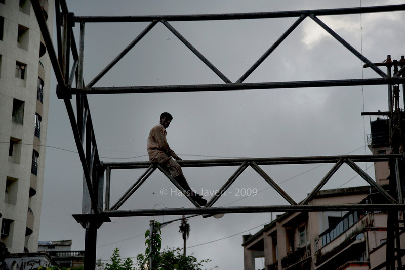 """Scaffolding (Pic 206 2nd year)<br /> <br /> This was shot on my Sunday walk. August-September have a lot of religious festivals in India.  It will start with Ganpati Visarjan and Pajusan in a few days.  The man was on top of  this scaffolding to make a shelter for pilgrims coming to Hare Krishna temple. <br /> <br /> It was an overcast evening and I've not done any PP except bring out some details on the buildings. <br /> <br /> Sorry for the late posting - it's Wednesday morning here - but had severe stomach pain with cramps and had to go to the hospital to carry out some tests. Feeling half way fine.... <br /> <br />  <a href=""""http://www.javeri.net"""">http://www.javeri.net</a>"""