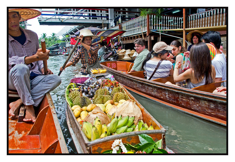 """4th year Pic 187 - July - 28 2012 <span style=""""color:yellow""""> Floating fruits! </span>, Damnoen Saduak , Thailand  Many of you had asked for more pictures of the floating market so here's one more! The lady is selling bananas, mangoes, duriyan, mangosteen and rambutan. Duriyan is the green spikey one and has such a strong smell that many hotels do not allow it inside the rooms! Black are mangosteen and at the end are the red rambutan. I do not know the name of the fruit between bananas & mangoes.   http://en.wikipedia.org/wiki/Durian<br> http://www.mangosteen.com/ <br> http://www.rambutan.com/<br> <span style=""""color:red""""> ADDED:  </span>Kenneth, like many other locals, she must lead a hard life. The floating village starts in the morning and closes soon after lunch and she must be getting her wares from a nearby village.  A floating market is where goods are sold from Thai style canoes. Originating in times and places where water transport played an important role in daily life, most floating markets operating today mainly serve as tourist attractions. Now shops on both sides of the canal plus plying boats offer fruits, vegetables, sweets and meats plus clothes, trinkets beside other things."""