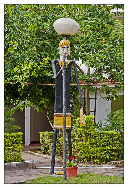 "4th year Pic 014 - Nov 11 2011 <span style=""color:yellow"">Lamppost </span> Naman Resort, Bastar, Chattisgarh  At the resort where we had stayed, they had lampposts in the shapes of local tribes. This one shows a turbaned man with a stick.  <span style=""color:red"">A note</span>   <span style=""color:yellow"">Standard Chartered Bank</span> are the main supporters of my daughter's sheltered workshop OM Creation. They have flown down some of the football players from <span style=""color:yellow"">Liverpool, UK </span>for a football clinic, to teach under privileged children. OM Creation is asked to do the lunch catering for three days and I was asked to take some photographs so I've just got back and am running late with work and getting the pics ready so please excuse my lack of comments.   Once again, thank you all for your comments!"