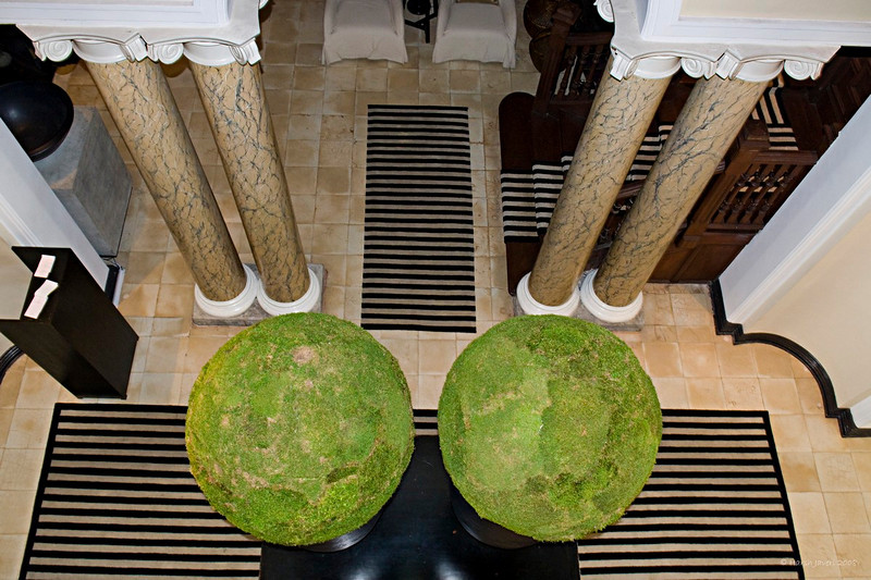 "219 28 Dec<br /> Looking down <br /> <br /> Tintagel Hotel, Colombo, Sri Lanka.<br /> D300 17-55 lens ISO 1000 f5.6 1/8 - Flash at Slow sync<br /> <br /> Dave, thanks for commenting on this pic in Colombo gallery! <br /> <br /> This is the view from the first floor (second for USA!) of the Tintagel hotel. We were on a 'tour' of the rooms and I had to hurry to cover the interesting decors of each room and other places. The green on the two orbs is sort of a lawn! Shooting was difficult because of the low light and I did not like the straight flash shot so used it with Slow Sync at a low speed. <br /> <br /> Do have a look at the rooms and the courtyard at<br /> <br />  <a href=""http://hershy.smugmug.com/gallery/6837782_hL4K3/1/437113249_NLbCH"">http://hershy.smugmug.com/gallery/6837782_hL4K3/1/437113249_NLbCH</a><br /> <br />  <a href=""http://www.javeri.net"">http://www.javeri.net</a>"