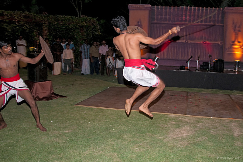"350<br /> Kalaripayattu 2 <br /> D300 ISO 400 f5.6 1/60 18-105mm lens<br /> <br /> The engagement dinner of Romita & Wilson had traditional Kerala cuisine and performances. I had never shot such action shots before and realised how difficult it is! To add to my woes, the flash batteries were dying! :(  I would have loved to experiment and take some shots with slow sync capturing a bit of a motion in the figures.  Still, I am quite happy with the results... <br /> <br /> <br /> Kalaripayattu - The Orient's treasure trove, a gift to the modern world and the mother of all martial arts. Legend traces the 3000-year-old art form to Sage Parasurama- the master of all martial art forms and credited to be the re-claimer of Kerala from the Arabian Sea. Kalaripayattu originated in ancient South India. Kung- fu, popularized by the monks of the Shoaling Temple traces its ancestry to Bodhi Dharma - an Indian Buddhist monk and Kalaripayattu master.<br /> <br />  <a href=""http://www.kalaripayattu.org/"">http://www.kalaripayattu.org/</a><br /> <br />  <a href=""http://www.javeri.net"">http://www.javeri.net</a>"