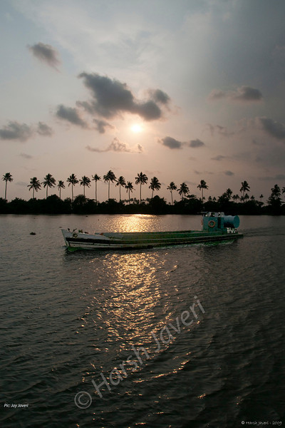"""362<br /> Sunset at Vembanad Lake<br /> <br /> At Kerala, hosts Daksha & Prem had organised boat rides for the guests on Vembanad Lake (Vembanad Kayal or Vembanad Kol), India's longest lake and also one of the largest lakes here. The Vembanad wetland system covers an area of over 1512 km and is approximately 14 kilometres wide at its widest point.. <br /> <br /> The ride was along the coast with a lot of greenery, something that Kerala is famous for. We also saw a couple of Houseboats on the way. With overcast sky the sunset was not a clear one. It was still scenic though!<br /> <br /> This shot is by son Jay. <br /> <br /> more pics of the boat ride: <br /> <br />  <a href=""""http://hershy.smugmug.com/gallery/8427608_pjpHZ/1/552585360_oXzjV"""">http://hershy.smugmug.com/gallery/8427608_pjpHZ/1/552585360_oXzjV</a><br /> <br /> more info: <br />  <a href=""""http://en.wikipedia.org/wiki/Vembanad_Lake"""">http://en.wikipedia.org/wiki/Vembanad_Lake</a><br /> <br />  <a href=""""http://www.javeri.net"""">http://www.javeri.net</a>"""