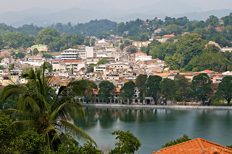 """228 Jan 06<br /> View of Kandy city <br /> D300 17-55mm ISO 400 f14 1/200<br /> <br /> In Sri Lanka, we made a short stop at Kandy en route from Galle to Tea Trails. Visited the Temple of Tooth and after a brief stroll had lunch at a restaurant overlooking the city.<br /> <br /> Kandy - a major tourist destination - is also known as the cultural capital of Sri Lanka. Nestled in the hills at an altitude of 488 m, it is located at a distance of 115 km from Colombo. A bustling commercial city, Kandy has a rich history. It was originally known as Senkadagala pura after a hermit named Senkada who lived there. Many of Sinhalese people call it Mahanuwara meaning the Great City. The name Kandy was derived by the colonial rulers from the word Kanda in Sinhala, meaning a hill.<br /> <br /> Today , Kandy is famous for the Kandy Perahara-a huge cultural pageant that takes place in the month of July or August. It is one of the most colorful processions of the world. Thousands of drummers and dancers accompanying a parade of ornamented elephants perform in the streets. The leading tusker carries the sacred tooth relic of Lord Buddha, while the spectators pay homage to it. The procession moves along the streets for seven consecutive nights and concludes on the day of the August full moon.<br /> <br /> The Temple of Tooth, also known as Dalda Maligawa, is one of the most sacred Buddhist pilgrimage sites in the world. Here, one of the Buddha's teeth is kept. The temple was built in the 17th century. A golden canopy has been added recently.<br /> <br /> There are many Buddhist temples surrounding Kandy and four Hindu shrines dedicated to Gods Vishnu and Natha and Goddess Patthini.<br /> <br /> More Kandy pictures at <br /> <br />  <a href=""""http://hershy.smugmug.com/gallery/6950360_Soc9F/1/444816807_ygkxM"""">http://hershy.smugmug.com/gallery/6950360_Soc9F/1/444816807_ygkxM</a><br /> <br />  <a href=""""http://www.javeri.net"""">http://www.javeri.net</a>"""