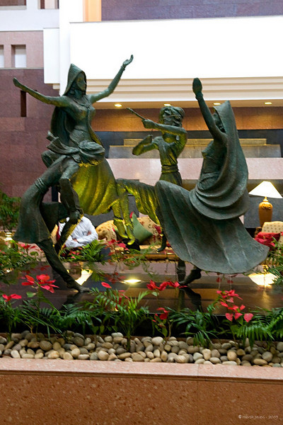 "295 - Mar 12<br /> Dancers <br /> <br /> This beautiful sculpture was in the main lobby of  Rajputana Sheraton hotel. The two lady dancers seemed to float in air. The man looking down is playing an Indian drum while the other is playing a string instrument. <br /> <br /> <br />  <a href=""http://www.javeri.net"">http://www.javeri.net</a>"