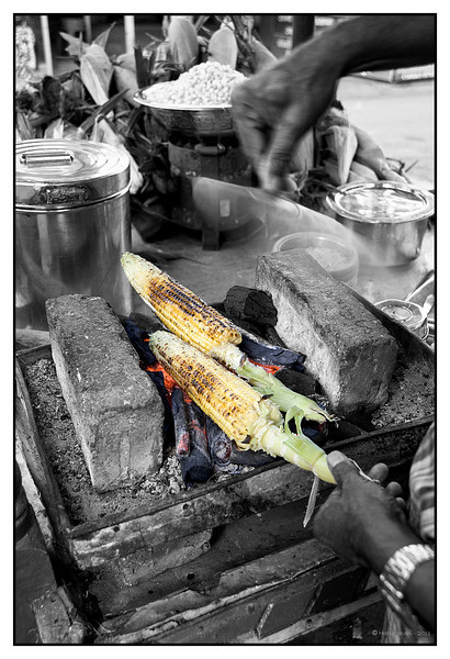 "3rd year Pic 165 - Feb 19 2011<br /> Corn on Cob<br /> Mahabaleshwar Market<br /> <br /> In India the corn is roasted on coal and when ready, lemon juice, pepper or red chili powder and salt are added to taste. In the picture the man is fanning the fire with a cardboard fan.  Some people prefer to apply a bit of butter too! Another way is to open the husks partially, apply the butter, close the husk flaps and let it 'bake' on coal heat. This gives a lovely charcoal flavour!<br /> <br /> The full colour version is here: <br />  <a href=""http://hershy.smugmug.com/Travel/Mahabaleshwar-2011-ppl/DSC4693/1178077335_tBFYc-XL.jpg"">http://hershy.smugmug.com/Travel/Mahabaleshwar-2011-ppl/DSC4693/1178077335_tBFYc-XL.jpg</a><br /> <br /> Thank you all for your comments on SC & full colour versions of Strawberry vendor yesterday!"