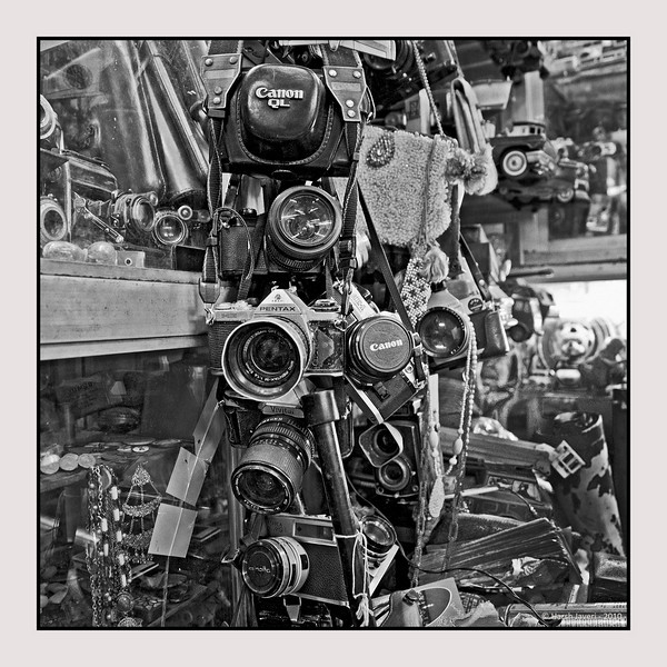 """3rd year Pic 083 - Oct 16 2010<br /> CLICK! Take your pick! <br /> <br /> This shop had all kinds of cameras! <br /> Check the colour version  :  <br />  <a href=""""http://hershy.smugmug.com/Photography/Mumbai-my-city/Chor-Bazar/13961726_aijBD#1035929850_kxUpy-A-LB"""">http://hershy.smugmug.com/Photography/Mumbai-my-city/Chor-Bazar/13961726_aijBD#1035929850_kxUpy-A-LB</a><br /> <br /> MANY THANKS TO ALL FOR THEIR BIRTHDAY WISHES YESTERDAY,  HERE AND AT FACEBOOK!!<br /> <br /> Chor Bazaar, located near Bhendi Bazaar in South Mumbai, is one of the largest flea markets in India. The word Chor means """"thief"""" in Hindi-Urdu. The reason it is known as """"thief's market"""", is because it assumed that goods sold there are stolen. There's a saying about this area, if you lose anything in Mumbai you can buy it back from the """"chor bazaar""""! Most of proper shops are closed on Friday as this area is in the heartland of one of the largest Muslim populations in Mumbai.<br /> <br /> Chor Bazar is a maze of streets with shops that look like musty attics and sell just about anything at bargain prices from old ship parts, grandfather clocks, gramophones, to crystal chandeliers and old English tea sets antiques at throwaway prices, including colonial-era lamps, Art Deco clocks and trinkets of every kind. It's not an easy job to shop here as one has to rummage through a lot of stuff, including junk and then set about bargaining.<br /> <br />  <a href=""""http://en.wikipedia.org/wiki/Chor_Bazar"""">http://en.wikipedia.org/wiki/Chor_Bazar</a>"""