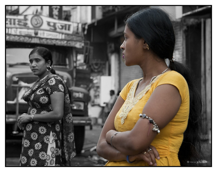 "3rd year Pic 128 - Jan 10 2011<br /> Ladies in waiting... <br /> Kamathipura, Mumbai<br /> <br /> Shot 'blind' with camera at waist level.<br /> <br /> Kamathipura is Mumbai's oldest & the world's largest red-light district. The area was set up by the British for their troops, which acted as their official ""comfort zone"". This small region boasted the most exotic consorts. In the 19th and early 20th centuries, a large number of women and girls from continental Europe and Japan were trafficked into Kamathipura, where they worked as prostitutes servicing both British soldiers and local Indian men. When the British left India, the Indian sex workers took over. In recent decades, large numbers of Nepalese women and girls have also been trafficked into the district as sex workers. Today, it is said that there are so many brothels in the area, that there is no space for the sex workers to sit in. They hang around in the streets, solicit customers and then rent an available bed.<br /> <br /> <br />  <a href=""http://en.wikipedia.org/wiki/Kamathipura"">http://en.wikipedia.org/wiki/Kamathipura</a><br /> <br /> 11th Jan: The woman in foreground is wearing a 'bajuband' - arm bracelet worn traditionally in west & north. Now it's used mainly for special <br /> occasions like weddings & festivals."