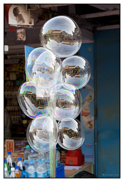 3rd year Pic 170 - Feb 24 2011<br /> Bubble reflections<br /> Mahabaleshwar Market<br /> <br /> Yes, they are bubbles! You get a tube with some gooey substance which you put on the end of a small plastic straw and blow from the other end. After the bubble is made you pinch it off and seal the hole. The bubble remains like that for a few hours and is a great novelty / toy for kids.<br /> <br /> Thanks to everyone for the comments on the lady's picture yesterday.