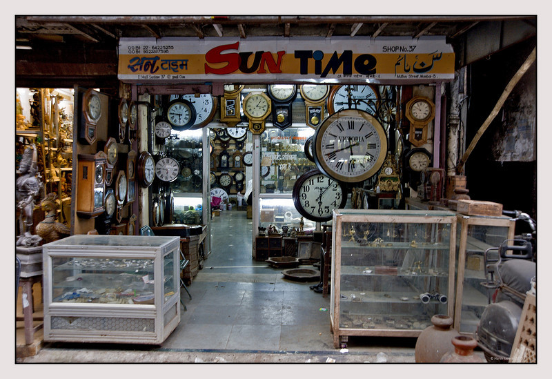 """3rd year Pic 086 - Oct 19 2010<br /> Time waits for no one... Shop at Chor Bazar<br /> <br /> Chor Bazaar, located near Bhendi Bazaar in South Mumbai, is one of the largest flea markets in India. The word Chor means """"thief"""" in Hindi-Urdu. The reason it is known as """"thief's market"""", is because it assumed that goods sold there are stolen. There's a saying about this area, if you lose anything in Mumbai you can buy it back from the """"chor bazaar""""! Most of proper shops are closed on Friday as this area is in the heartland of one of the largest Muslim populations in Mumbai.<br /> <br /> Chor Bazar is a maze of streets with shops that look like musty attics and sell just about anything at bargain prices from old ship parts, grandfather clocks, gramophones, to crystal chandeliers and old English tea sets antiques at throwaway prices, including colonial-era lamps, Art Deco clocks and trinkets of every kind. It's not an easy job to shop here as one has to rummage through a lot of stuff, including junk and then set about bargaining.<br /> <br /> To TDM: <br /> No, the watch repairer wasn't anywhere near! The shop keeper wouldn't have liked it - get out of the shop and go to the repairer!?! :-)<br /> <br />  <a href=""""http://en.wikipedia.org/wiki/Chor_Bazar"""">http://en.wikipedia.org/wiki/Chor_Bazar</a>"""