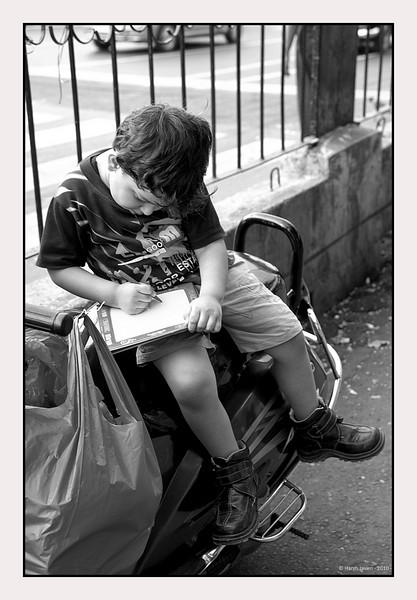 "3rd year Pic 098 - Oct 31 2010<br /> Engrossed<br /> near Victoria Terminus (VT) Station now known as Chatrapati Shivaji Terminus (CST)<br /> <br /> Sitting alone on the scooter, he was engrossed drawing on his etch-a-sketch pad.  Felt the bright colours in the original version were slightly distracting so converted  to B&W. <br /> <br /> The original colour version is here: <br />  <a href=""http://hershy.smugmug.com/Photography/Mumbai-my-city/Misc-shots-of-Mumbai/6410100_x8urE#1037279265_PHvgH-A-LB"">http://hershy.smugmug.com/Photography/Mumbai-my-city/Misc-shots-of-Mumbai/6410100_x8urE#1037279265_PHvgH-A-LB</a>"