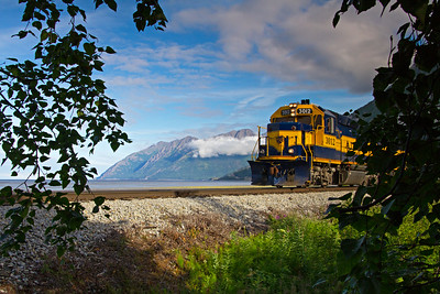 A southbound train heads for Whittier on a beautiful Alaska day along the shores of Turnagain Arm.