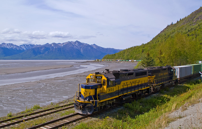 My previous train photo in Alaska was so well received, thank you, I thought I would post another one. This shot shows a long freight train at Indian along Turnagain Arm, while the tide is out, headed for the barge at Whittier, AK