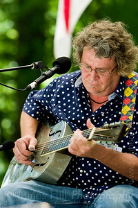 "Lightnin' Wells performing on the Grove Stage at the 2009 Festival for the Eno.    Straight from Lightnin's myspace page: ""Mike ""Lightnin'"" Wells breathes new life into the vintage tunes of the 1920s and depression era America employing various appropriate stringed instruments in a dynamic style which he has developed in over thirty years of performing experience. Raised in eastern North Carolina, Wells learned to play harmonica as a young child and taught himself to play the guitar as he developed a strong interest in traditional blues and folk music...."""
