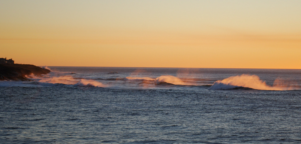 The sunset catches the mist off of waves,