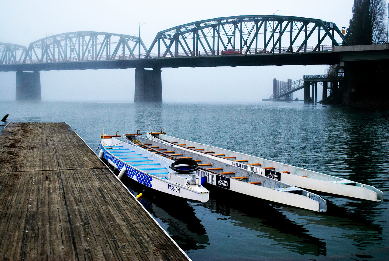 Dragon boats await rowers on a foggy morning