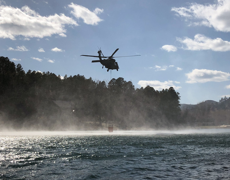 Helicopter dipping water buckets in Canyon Lake during the Schroeder Fire