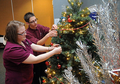 Lorain County JVS allied health and science students Samantha Soltis, left, of North Ridgeville,and Tyler Perry of Amherst decorate Christmas trees at  Riverview Pointe Nursing Home in Olmsted Falls on Dec. 8.  STEVE MANHEIM/CHRONICLE