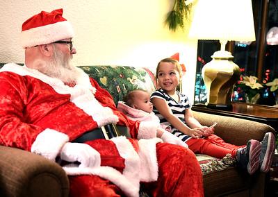 KRISTIN BAUER | CHRONICLE          Alana Payne, 4, of Elyria, smiles while sitting next to her sister Salina Alicea, 6 mos, while meeting Santa at Finwood Estate, in Elyria, on Wednesday night, Dec. 2.
