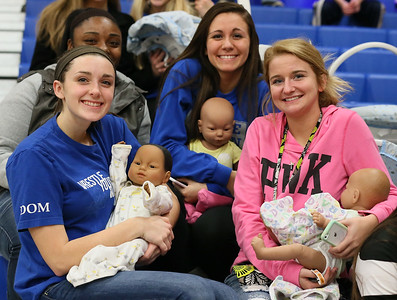 """Midview students Jamie Verda, left, Brianna Martinez, and Alaina Davidson hold their """"babies"""" at the Midview basketball game. The babies are part of a school lesson. RAY RIEDEL/CHRONICLE"""