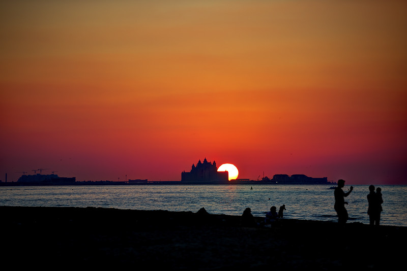 Sun setting behind the Atlantis Hotel on the Palm as seen from Kite Beach in Dubai.
