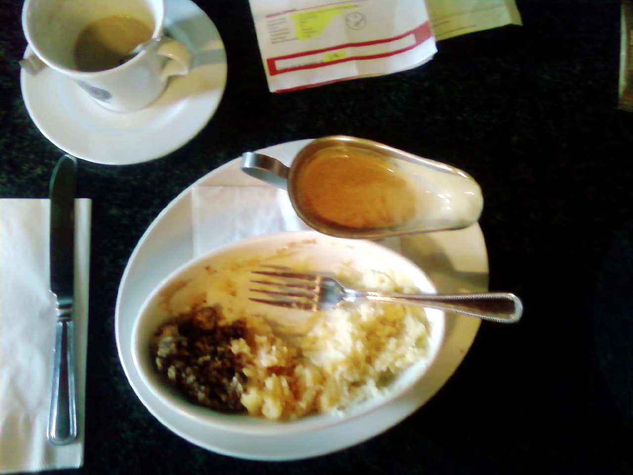 Half-eaten haggis. I meant to take a picture before I started eating it, but I couldn't resist it long enough.<br /> <br /> That's the haggis on the left of the dish. The middle is cauliflower, I think. The right is mashed potatoes.