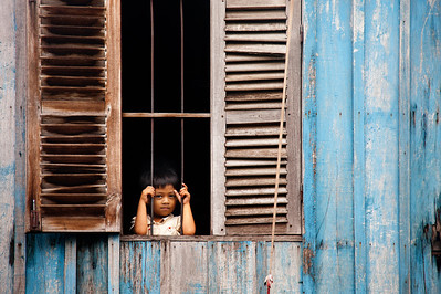 Peeking boy through windows and blue walls. Cambodia. 2011