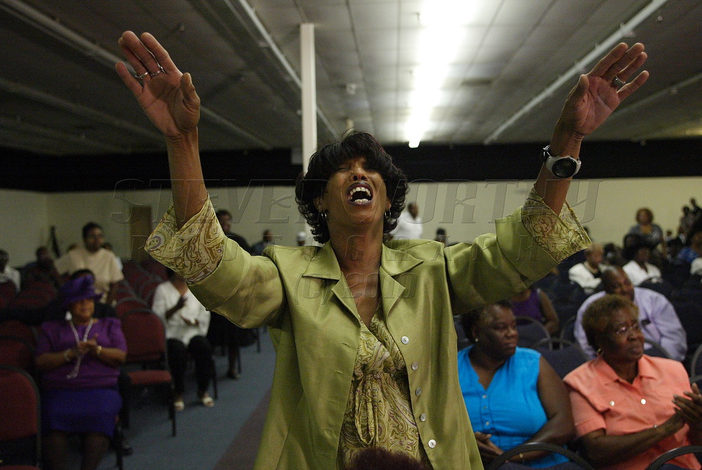 A patron shows her praise during the James Thomas singing anniversary at The Lighthouse Center in Raleigh, September 2007.