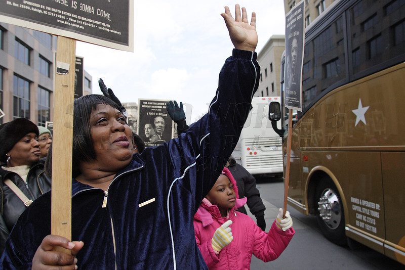 Marcher, in the 2009 MLK memorial march, waves to buses leaving for inauguration ceremony of Barack Obama on Jan 19th , 2009 in Downtown Raleigh.