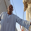 Assistant handling sails on felucca boat.