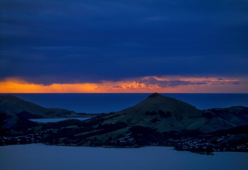 Pacific sunrise behind Otago Peninsula in Dunedin on the south island of New Zealand. <br /> Photo © Carl Clark