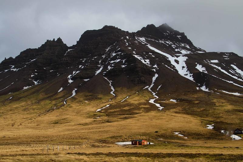 A remote cabin under stark hills on the Vesturland peninsula.<br /> Photo © Carl Clark