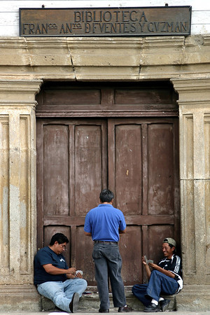Men playing cards in front of the library- Antigua, Guatemala