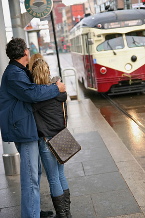 Couple waiting in the rain for a MUNI Streetcar along the Embarcadero- San Francisco, CA