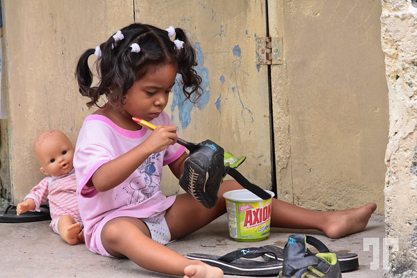 Hard at work<br /> <br /> <br /> Posted: Apr 28, 2012<br /> <br /> This is the same Caribbean girl a few seconds before the other photo was taken, when she hadn't noticed me yet.<br /> When she saw me, I asked her in my poor Spanish if she was fixing her father's shoes.<br /> <br /> Straight from the camera  Bocas Del Toro, Panama  (ZZ)