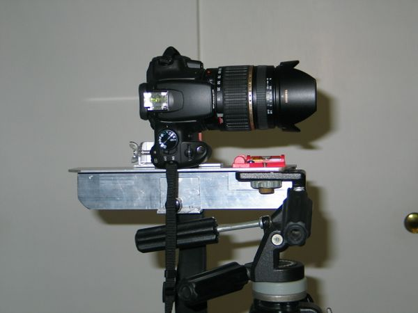 Camera mounted on bracket, the red thing is a level to make sure that the tripod is level. The bracket holds the camera in the vertical position and the vertical axis of rotation is through the nodal point.