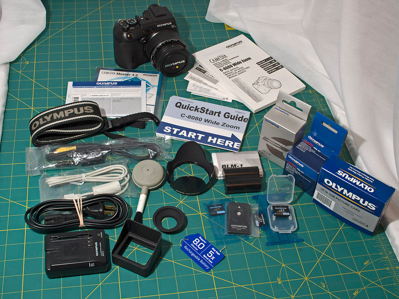 OLYMPUS DIGITAL CAMERA For sale – Olympus C-8080 camera with 28-140 mm f/2.4-f/3.5 lens<br /> Original accessories: original box, Olympus lens hood LH-3, Olympus BCM-2 battery charger and cord, BLM-1 Lithium Ion rechargeable battery, Olympus 32 MB xD card, new, Olympus RM-2 remote control, new, Original USB cable, new, Original video connection cable, new, Olympus camera strap, All original manuals, documents and warranty cards, new & unused, Olympus Master 4.2 CD with manual and RAW file conversion software, new