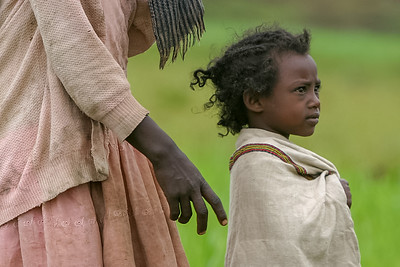 A young woman walking with her mother in the the fields outside Addis Ababa, Ethiopia
