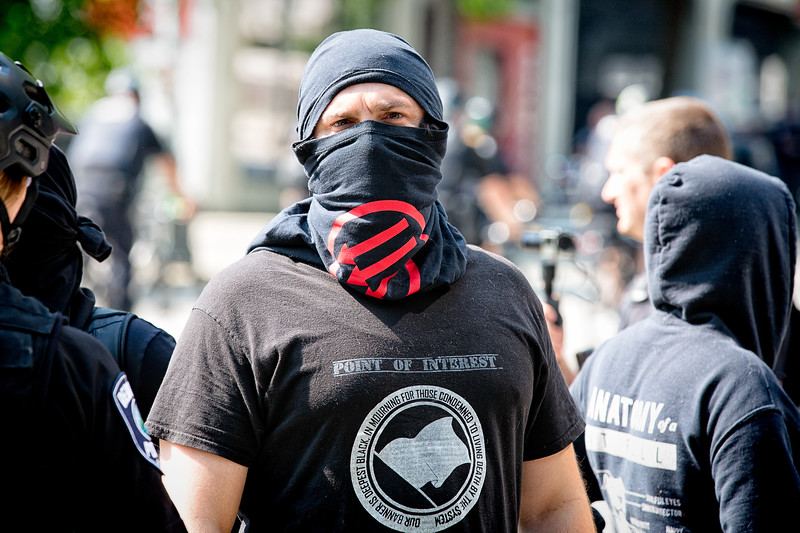 Anti-fascist protester glares at the far-right supporters on the other side of the police officers.