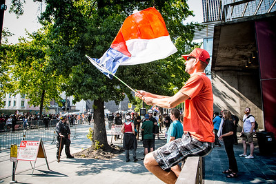 A far-right supporter waves a flag back and forth at the counterprotesters across the street from Seattle City Hall.