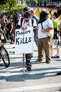 "An anti-fascist protestor crosses the street with his ""Fascism Kills"" sign."