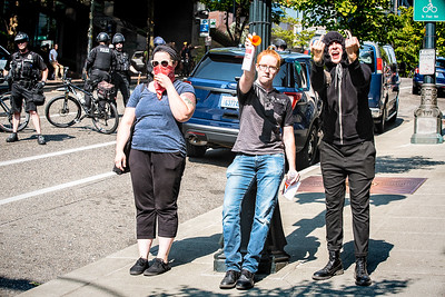 Three anti-fascists I encountered upfront after taking their picture. I was asked to delete the photo, but I refused, mainly because of their attitude, and because they denied I had the right to take their photo in a public place. The two on the left were making such a ruckus that I pointed at that they were likely causing more people to take their picture. The individual in all-black, giving me the double-finger, wanted to take my photo and asked me her name. I didn't give her my name because I thought it was quite rude to demand someone tell you their name without first introducing themselves. She attempted to take my photo by placing her phone five inches from my face. Then she told me to back up so she could take the shot. I refused, telling her to back up and take the shot. At this point I began thinking about going to the dark side, instead I told the two on the right that they were part of the problem. At that point the air horn went off and I was rewarded with two birds, which prompted me to take even more photos.